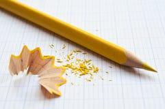 Gelber Bleistift und Bleistiftschnitzel auf Notizbuch Lizenzfreie Stockfotografie