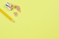 Gelber Bleistift und Bleistiftspitzer auf einem Gelb Stockfotografie