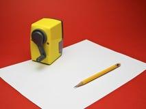 Gelber Bleistift und Bleistiftspitzer auf Weißbuch mit rotem Hintergrund Stockfoto
