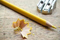 Gelber Bleistift und Schnitzel auf hölzernem Hintergrund Stockfotografie
