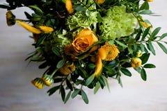 Gelber Blumenstrauß mit grüner Gartennelke, in der Zusammensetzung von Chrysanthemen, von Rosen und von gefärbten Körnern Stockfoto