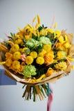 Gelber Blumenstrauß mit grüner Gartennelke, in der Zusammensetzung von Chrysanthemen, von Rosen und von gefärbten Körnern Lizenzfreies Stockfoto
