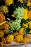 Gelber Blumenstrauß mit grüner Gartennelke, in der Zusammensetzung von Chrysanthemen, von Rosen und von gefärbten Körnern Stockfotos