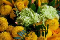 Gelber Blumenstrauß mit grüner Gartennelke, in der Zusammensetzung von Chrysanthemen, von Rosen und von gefärbten Körnern Lizenzfreie Stockfotos