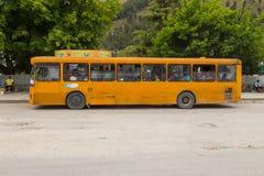 Gelber Bus auf den Straßen der Stadt von Berat, Albanien stockbild