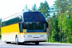 Gelber Bus auf einem Waldweg Stockfotos