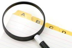 Gelber Dateiteiler und -vergrößerungsglas Stockfotografie