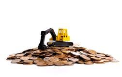 Gelber Exkavator auf einem großen Haufen der Münzen Stockfotos