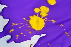 Gelber Fleck auf zerfließender purpurroter Farbe Stockfoto