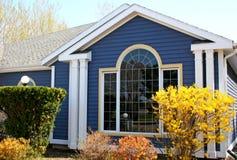 Gelber Forsythia u. blaues Haus Stockfotos
