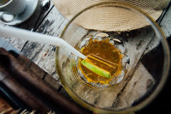 Gelber Fruchtcocktail mit Eis und Scheibenkalk im Glas mit einem Stroh Stockfoto