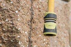 Gelber Gartenschlauch mit der Festlegungskoppelung mit der Aufschrift Lizenzfreies Stockfoto