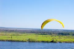 Gelber Gleitschirm im blauen Himmel über dem Fluss und dem Flussufer Vogel ` s Augenpanorama Tom River Tomsk-Stadt, Russland Lizenzfreie Stockbilder