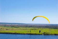 Gelber Gleitschirm im blauen Himmel über dem Fluss und dem Flussufer Vogel ` s Augenpanorama Tom River Tomsk-Stadt, Russland Stockbild