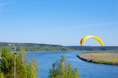 Gelber Gleitschirm im blauen Himmel über dem Fluss und dem Flussufer Vogel ` s Augenpanorama Tom River Tomsk-Stadt, Russland Stockbilder