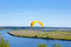 Gelber Gleitschirm im blauen Himmel über dem Fluss und dem Flussufer Vogel ` s Augenpanorama Tom River Tomsk-Stadt, Russland Lizenzfreie Stockfotografie