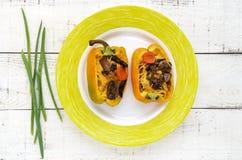 Gelber grüner Pfeffer angefüllt mit Pilzen, Gemüse und Käse auf einer Platte Stockfoto