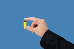 Gelber greller Antrieb an Hand mit lokalisiertem blauem Hintergrund Lizenzfreies Stockbild