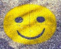 Gelber gro?er smiley mit lachendem Gesicht auf dem Fu?weg stockfotos