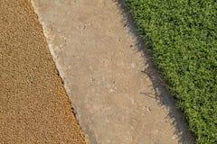 Gelber Gummi-Wetpour-Spielplatzfußbodenbelag nahe bei konkretem und künstlichem Gras Stockbilder