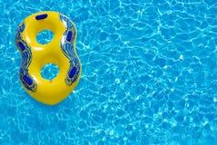 Gelber Gummiring, der auf blaues Wasser schwimmt Stockbilder