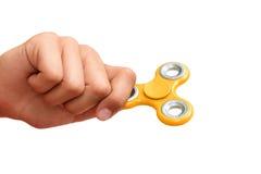 Gelber Handspinner Junge, der einen populären Spielzeugunruhespinner in seiner Hand spielt Entspannung Antidruck und Entspannung Stockfotografie