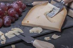 Gelber, harter holländischer Käse und rote Trauben auf einer Steinplatte stockfotografie