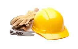Gelber harter Hut, Handschuhe und Hammer auf Weiß Stockbilder