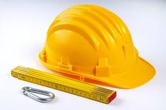 Gelber harter Hut mit Carabiner und hölzernem Tabellierprogramm Stockfotos