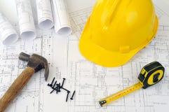 Gelber harter Hut und Haufen der Projektzeichnungen Lizenzfreies Stockbild