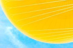 Gelber Heißluft-Ballon auf blauem Himmel Stockfotos