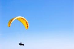 Gelber heller Gleitschirm im blauen Himmel Stockfoto
