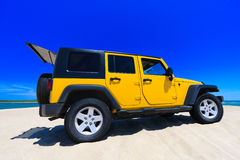Gelber Jeep auf dem Strand Stockfoto