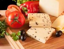 Gelber Käse mit Olive auf Schneidebrett Stockbilder