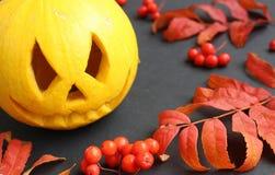Gelber Kürbis für Halloween in den hellen Blättern des Herbstes stockfotos