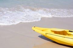 Gelber Kajak auf dem Strand Stockbilder