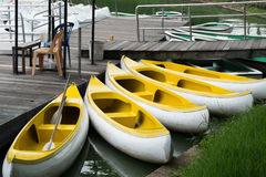 Gelber Kanuliegeplatz auf dem hölzernen Hafen Stockbilder