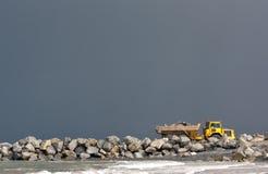 Gelber Kipper-LKW, der Küstenverteidigungarbeiten aufbaut Lizenzfreies Stockfoto