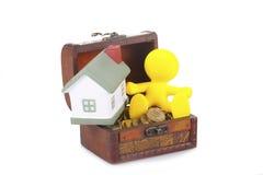 Gelber kleiner Mann des Spielzeugs sitzt auf einem Kasten Lizenzfreie Stockfotografie