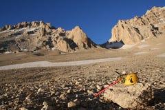 Gelber kletternder Sturzhelm und rote Eisaxt, liegend auf einem Felsen in den Bergen Stockfotos