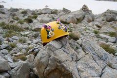 Gelber kletternder Sturzhelm verziert mit den Blumen, liegend auf einem Felsen in den Bergen Stockfoto