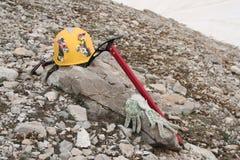 Gelber kletternder Sturzhelm verziert mit den Blumen, liegend auf einem Felsen in den Bergen Lizenzfreies Stockbild