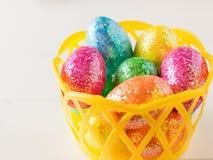 Gelber Korb mit bunten Eiern auf einer weißen rustikalen Tabelle Stockfoto