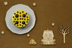 Gelber Kuchen auf einer weißen Servierplatte Auf dunklen Hintergrund Ikonen: Holz Stockfotografie