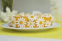 Gelber Kuchen mit Gänseblümchenblumen stockbild