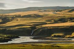 Gelber Landschaftshügel mit kleinem Wasserfall und Fluss in der Front wenn Note das Licht Stockbild