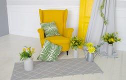 Gelber Lehnsessel im Innenraum mit Elementen von Heimtextilien, von Kissen und von Blumendekor Stockfotografie