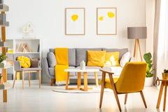 Gelber Lehnsessel im weißen Wohnzimmerinnenraum mit Poster oben stockfoto