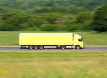 Gelber LKW, der auf eine Straße fährt Lizenzfreie Stockfotos