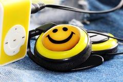 Gelber Musikspieler und schöne obenliegende Kopfhörer, Lächeln stockfoto